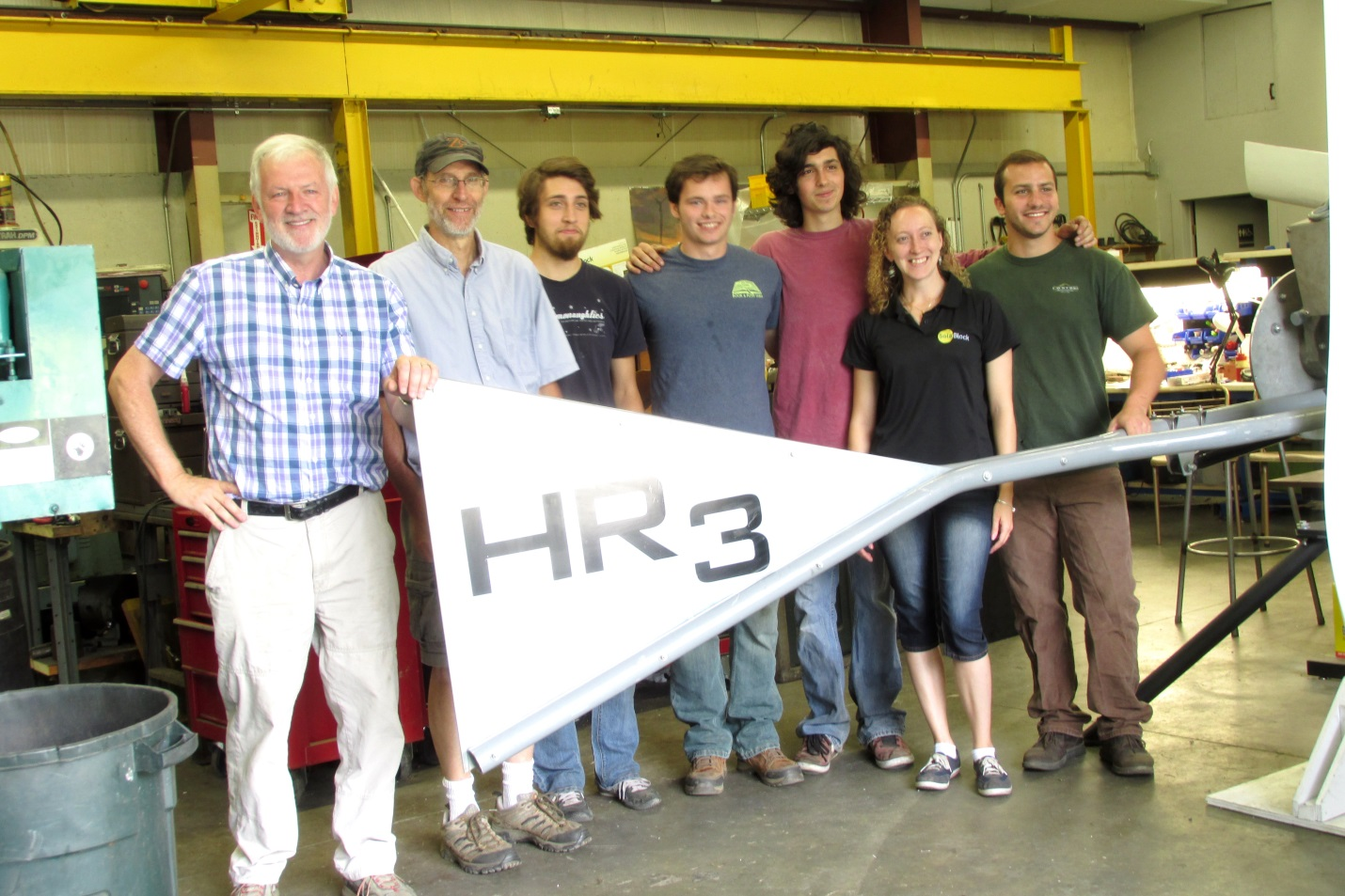 The staff of Black Island Wind Turbine poses with their turbine blade.